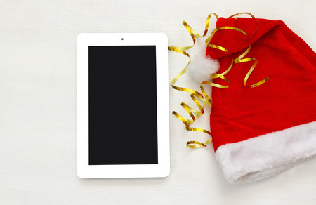 christmas hat: On line christmas holiday shopping concept. Santa claus red hat next to tablet device