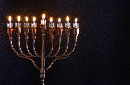 hanuka: Low key Image of jewish holiday Hanukkah background with menorah (traditional candelabra) and burning candles