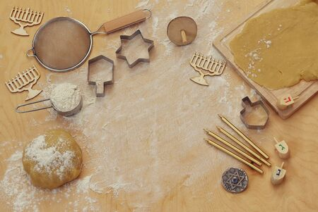 jewish cuisine: top view image of jewish holiday Hanukkah concept. Baking donuts and cookies on wooden kitchen table   Stock Photo