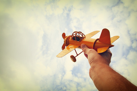 airplane: close up photo of mans hand holding retro airplane against blue sky. Filtered image