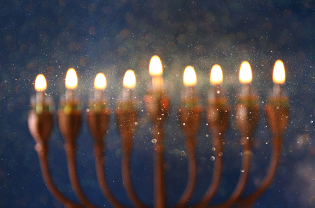 hanukiah: abstract and blurry image of jewish holiday Hanukkah background with menorah (traditional candelabra) and burning candles