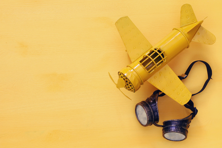 planes: Top view of vintage yellow toy plane and pilot glasses. Stock Photo
