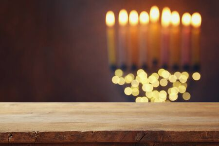 hanukah: Empty wooden table in front of jewish holiday Hanukkah background with menorah (traditional candelabra) and burning candles Stock Photo