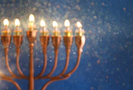 chanukiah: abstract and blurry image of jewish holiday Hanukkah background with menorah (traditional candelabra) and burning candles