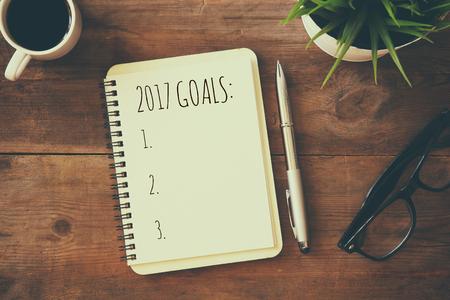 Bovenaanzicht 2017 lijst doelen met een notebook, kopje koffie op houten bureau