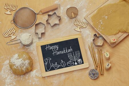 judaic: top view image of jewish holiday Hanukkah concept. Baking donuts and cookies on wooden kitchen table   Stock Photo