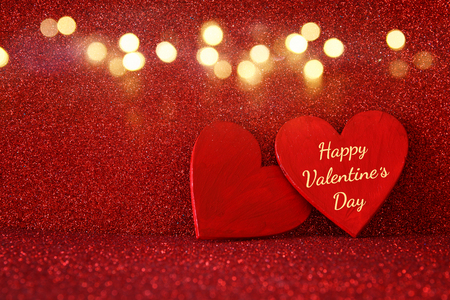 Valentines day background. Wooden red hearts on red shiny background