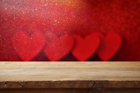 valentines background: Valentines day background. Empty wooden table in front of glitter red hearts background. For product display montage Stock Photo