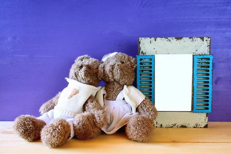 juguetes de madera: Foto de la pareja lindo oso de peluche junto al marco vacío en la mesa de madera. Para la fotografía de montaje. Retro filtrada y tonificado