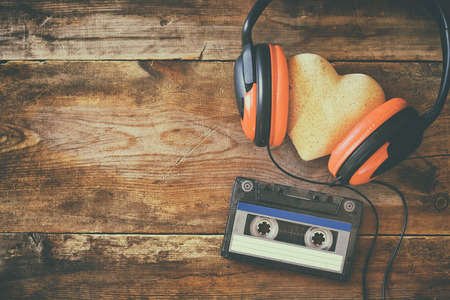 beating: Top view of headphones with fabric heart next tape cassette over wooden background. Retro filtered