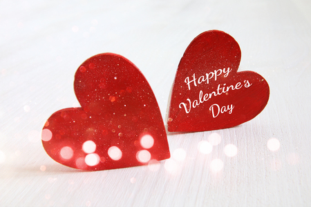 valentines background: Valentines day background. Couple of red wooden hearts. Glitter overlay Stock Photo