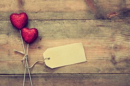 Valentijnsdag achtergrond. Paar van rode glitter harten en lege tag voor kopie ruimte op houten achtergrond. Plat samenstelling