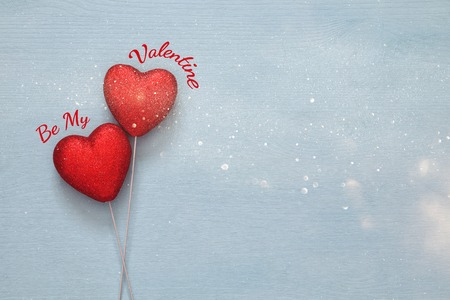 valentines background: Valentines day background. Couple of red glitter hearts on wooden background. Flat lay composition Stock Photo