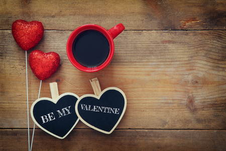 Valentines day background. Couple of red glitter hearts and chalkboard on wooden background. Flat lay composition Stock Photo