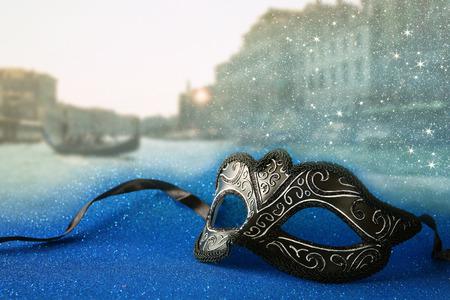 mardigras: Image of elegant venetian mask in front of blurry Venice background. Glitter overlay