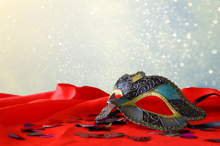 sexual: Image of elegant venetian mask on red silk and glitter shiny background