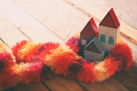 juguetes de madera: Image of wooden colorful houses wrapped in cozy warm scarf over the table Foto de archivo