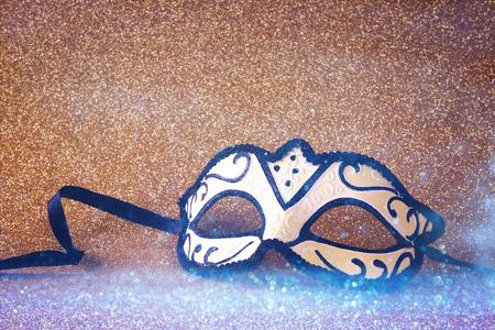 mardigras: Image of elegant venetian mask on gold glitter background Stock Photo