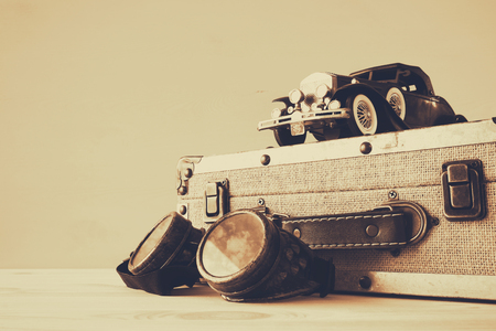 dream car: Foto del coche de juguete de la vendimia y la maleta vieja junto a las gafas piloto sobre la mesa de madera. sepia filtrada Foto de archivo