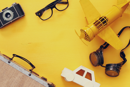 Top view of vintage yellow toy plane, old photo camera, pilot glasses and suitcase