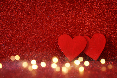 glitz: Valentines day background. Wooden red hearts on red shiny background