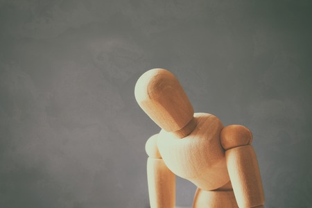 ocd: image of wooden dummy with worried stressed body position. depression, obsessive compulsive, adhd, anxiety disorders concept