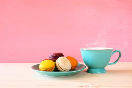 coffee and cake: Mint vintage cup of coffee and colorful macaron or macaroon on wooden table over pink background