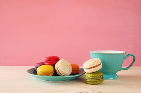 Mint vintage cup of coffee and colorful macaron or macaroon on wooden table over pink background