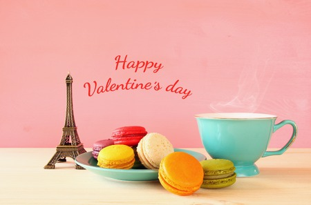 Mint vintage cup of coffee and colorful macaron or macaroon next to Eiffel Tower on wooden table over pink background