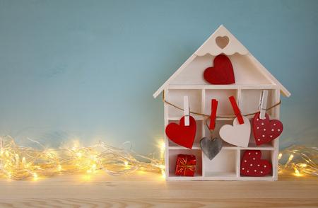juguetes de madera: Fondo del día de San Valentín. casa de madera con muchos corazones y guirnalda luces sobre la mesa Foto de archivo