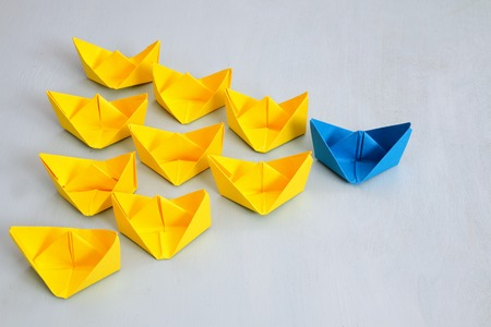 Leadership concept with paper boats on blue wooden background. One leader ship leads other ships. Filtered and toned image Reklamní fotografie - 68852417