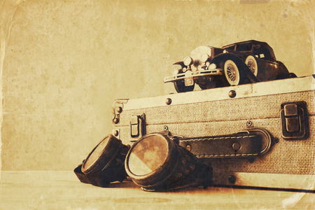 vintage photo: Photo of vintage toy car and old suitcase next to pilot glasses on wooden table. Sepia style filtered and textured image Stock Photo