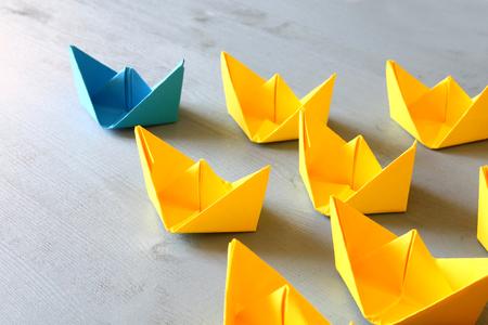 Leadership-Konzept mit Papier Boote auf blauem Holzuntergrund. Ein Führer Schiff führt andere Schiffe. Gefiltert und getöntes Bild