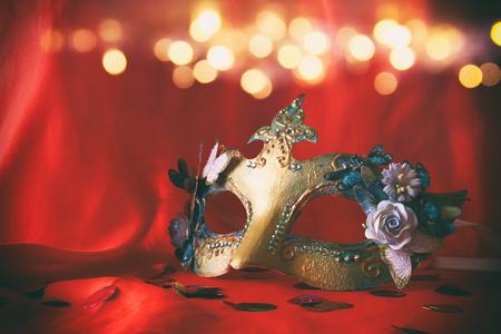 carnivale: Image of elegant venetian mask on red silk background Stock Photo