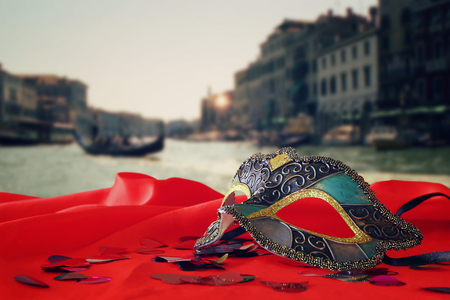 party night: Image of elegant venetian mask on red silk fabric in front of blurry Venice background