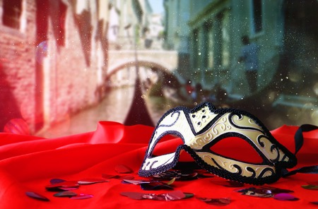 venice mask: Image of elegant venetian mask on red silk fabric in front of blurry Venice background. Glitter overlay Stock Photo