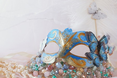 Image of delicate blue elegant venetian mask next to pearls and jewel in front of white tulle background Stock Photo