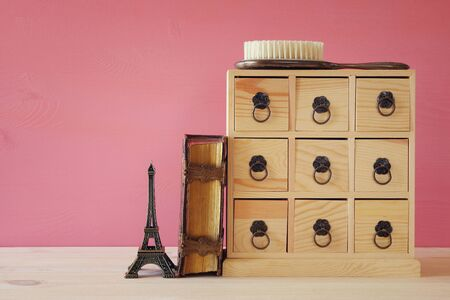 old furniture: Image of natural wooden antique chest with drawers next to old book and eiffel tower and metal handles