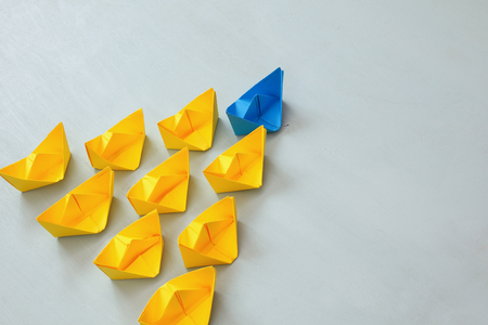 Leadership concept with paper boats on blue wooden background. One leader ship leads other ships. Filtered and toned image Banque d'images