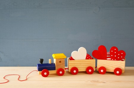 wooden toy: Wooden toy train with herts on the table. Stock Photo