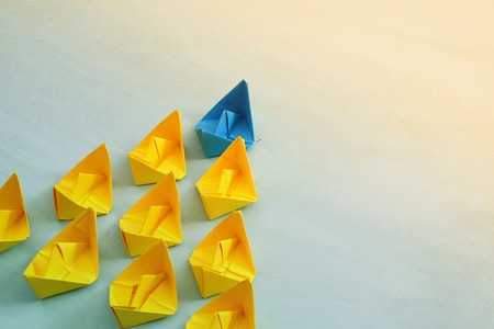 Leadership concept with paper boats on blue wooden background. One leader ship leads other ships. Filtered and toned image Foto de archivo