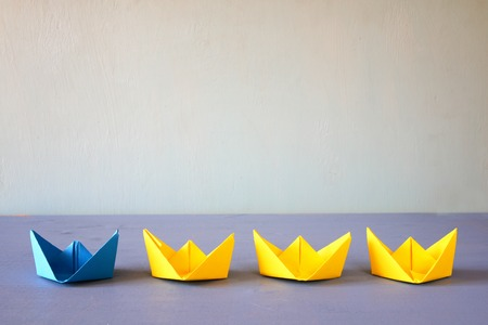 supervisión: Leadership concept with paper boats on blue wooden background. One leader ship leads other ships. Filtered and toned image Foto de archivo