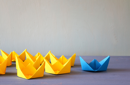 Leadership concept with paper boats on blue wooden background. One leader ship leads other ships. Filtered and toned image Stock Photo