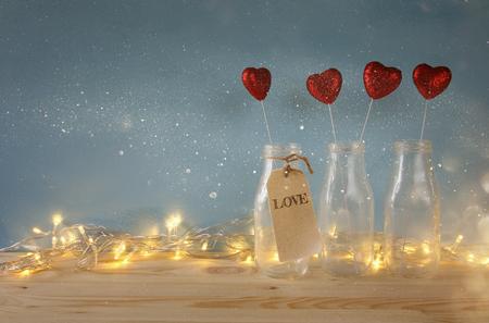 Valentijnsdag achtergrond. Glitter harten in de glazen vazen op houten tafel
