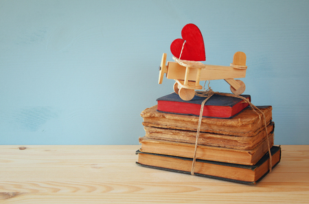old books: Valentines day background. Wooden plane with heart on the stack of old books