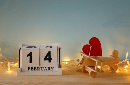 Valentines day background. Wooden plane with heart next to calendar on the table