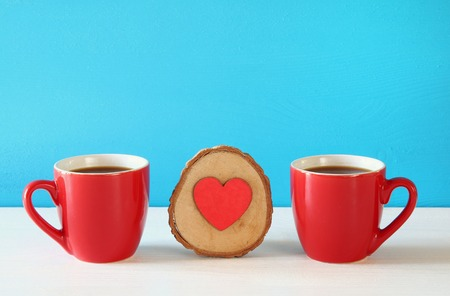 tea table: Wooden heart next to coffee cups on wooden table. Stock Photo