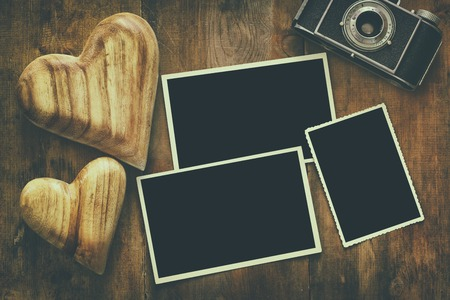 photo frame: Top view of empty photo frames next to old camera and hearts over wooden table. Ready to put photographs. Flat lay. Retro filtered Stock Photo