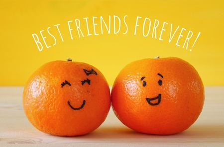 clementines: Image of two cute clementines with drawn smiley faces on wooden table. Best friend concept Stock Photo