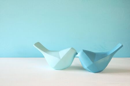 Couple of Lovebirds on wooden table in front of blue pastel background Stock Photo